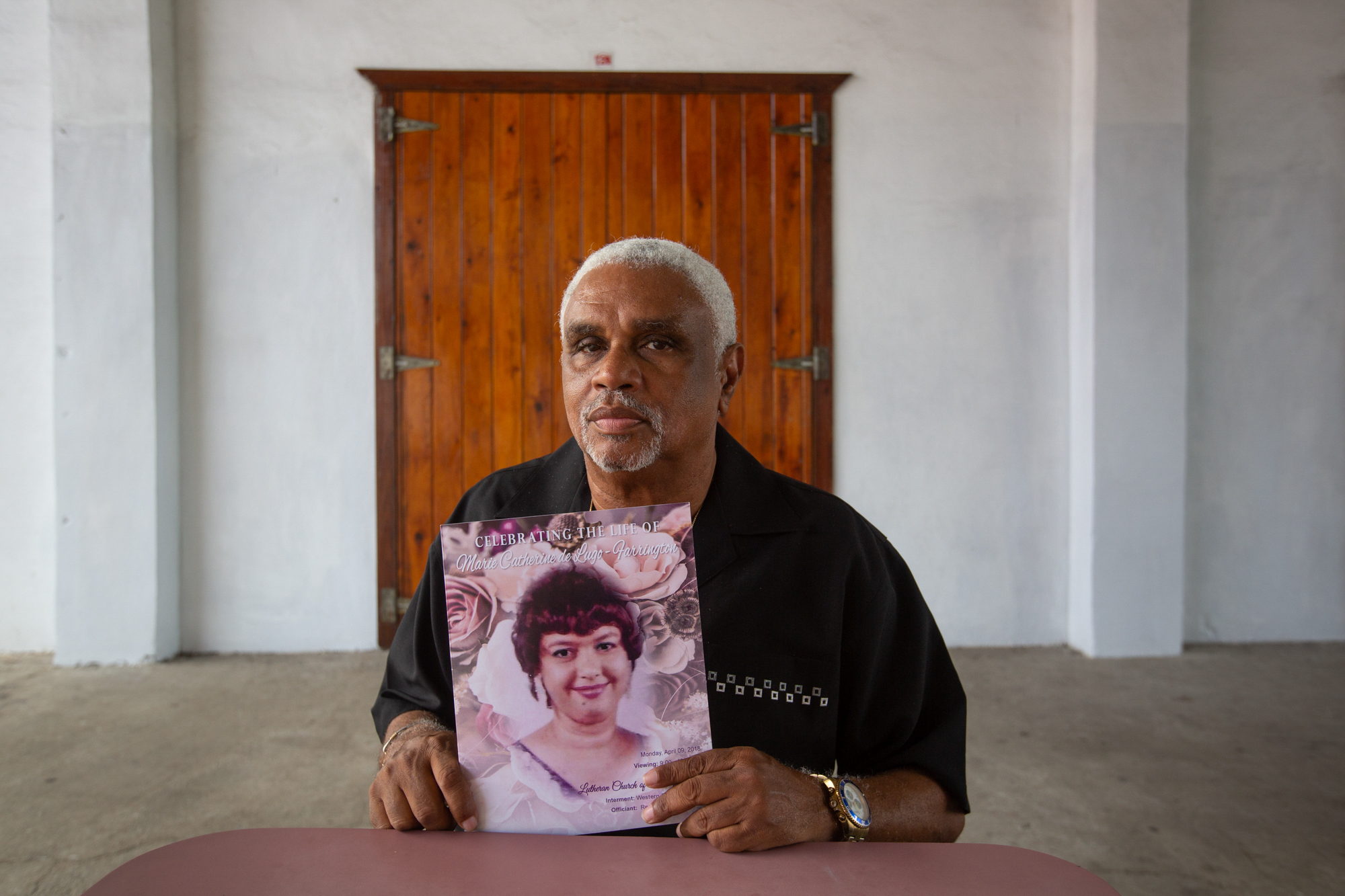 Michael Farrington - Michael Farrington of St. Thomas, U.S. Virgin Islands, holds a copy of his wife's funeral program. Marie Catherine de Lugo-Farrington was medically evacuated to Puerto Rico before Hurricane Irma, then evacuated to the mainland before Hurricane Maria hit Puerto Rico. She died shortly after Farrington brought her home to St. Thomas. He says FEMA did a poor job of tracking patients who were medically evacuated. (Anya Magnuson/News21)