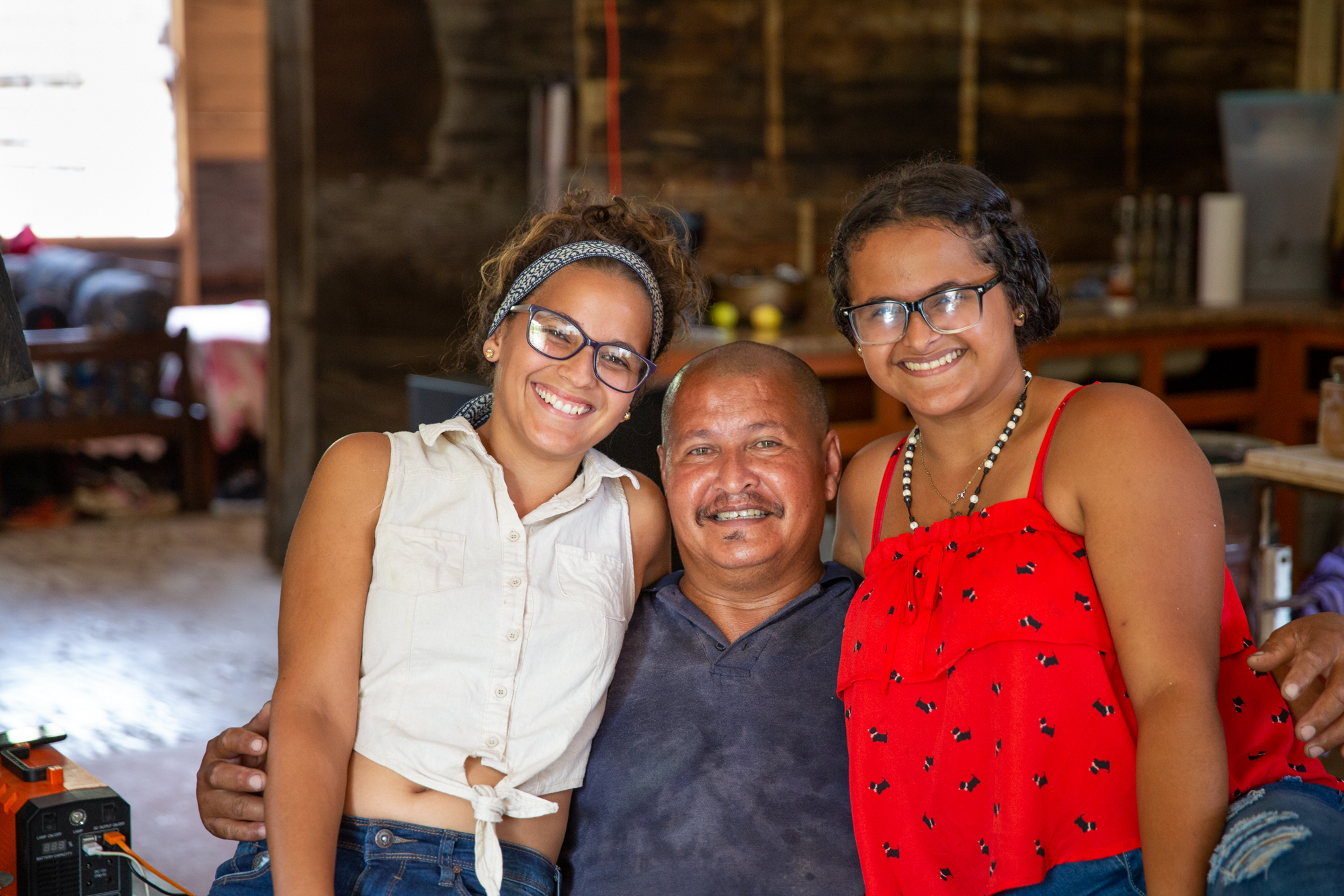 Roberto Cornier and family - Roberto Cornier had 11 strokes in 2017 and was evicted from his home in Peñuelas, Puerto Rico, after Hurricane Maria. His daughters Kenaisha, 21 (left), and Gabriela, 15, took him to the hospital and found a new place for the family to stay – a derelict, abandoned school. (Ellen O'Brien/News21)