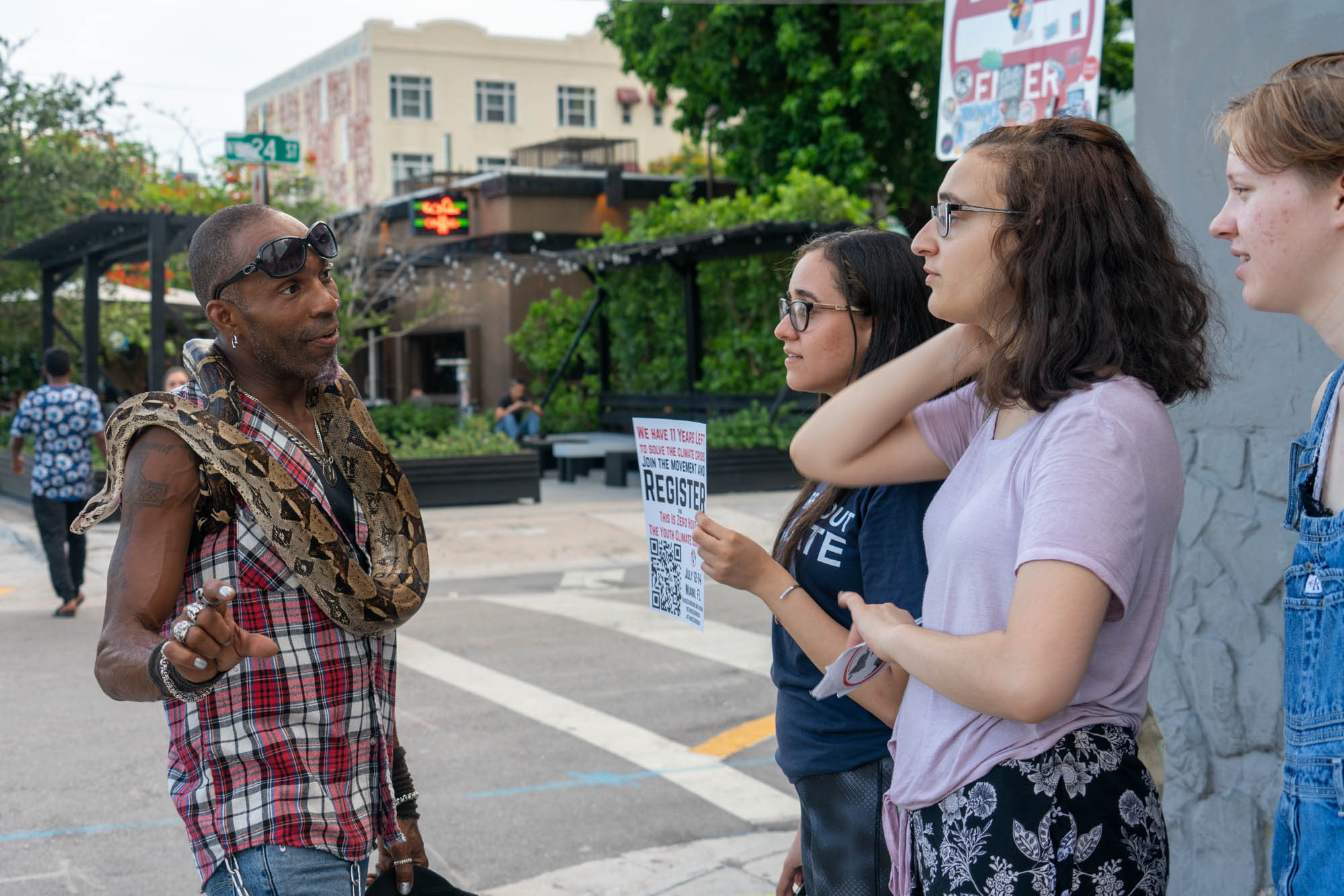 "Ray ""Fangdaddy"" Henry, a street performer in Miami's Wynwood Walls district, learns about the Youth Climate Summit from Zero Hour activists (from left) Sohayla Eldeeb, Jamie Margolin and Kendall Kieras. (Jordan Laird/News21)"