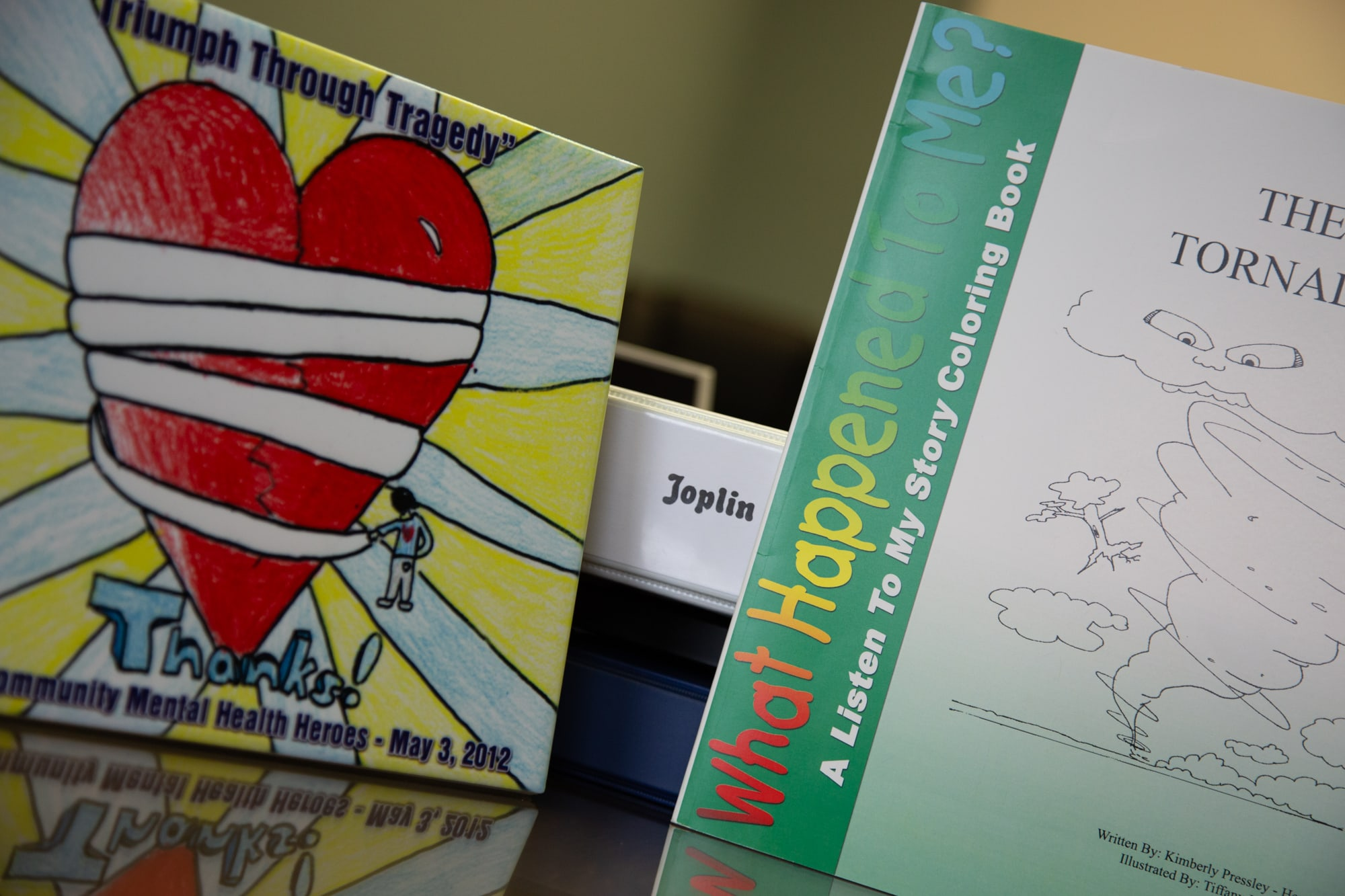 The Healing Joplin program included a coloring book to help young children  process how a tornado can affect them. To the left is a tile depicting a child's drawing that was submitted in a Healing Joplin art contest. (Brigette Waltermire/News21)